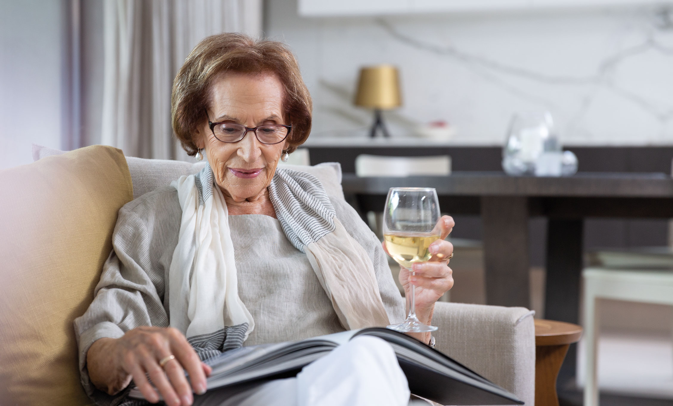 Senior woman drinking white wine, reading a magazine, Europa on Alma