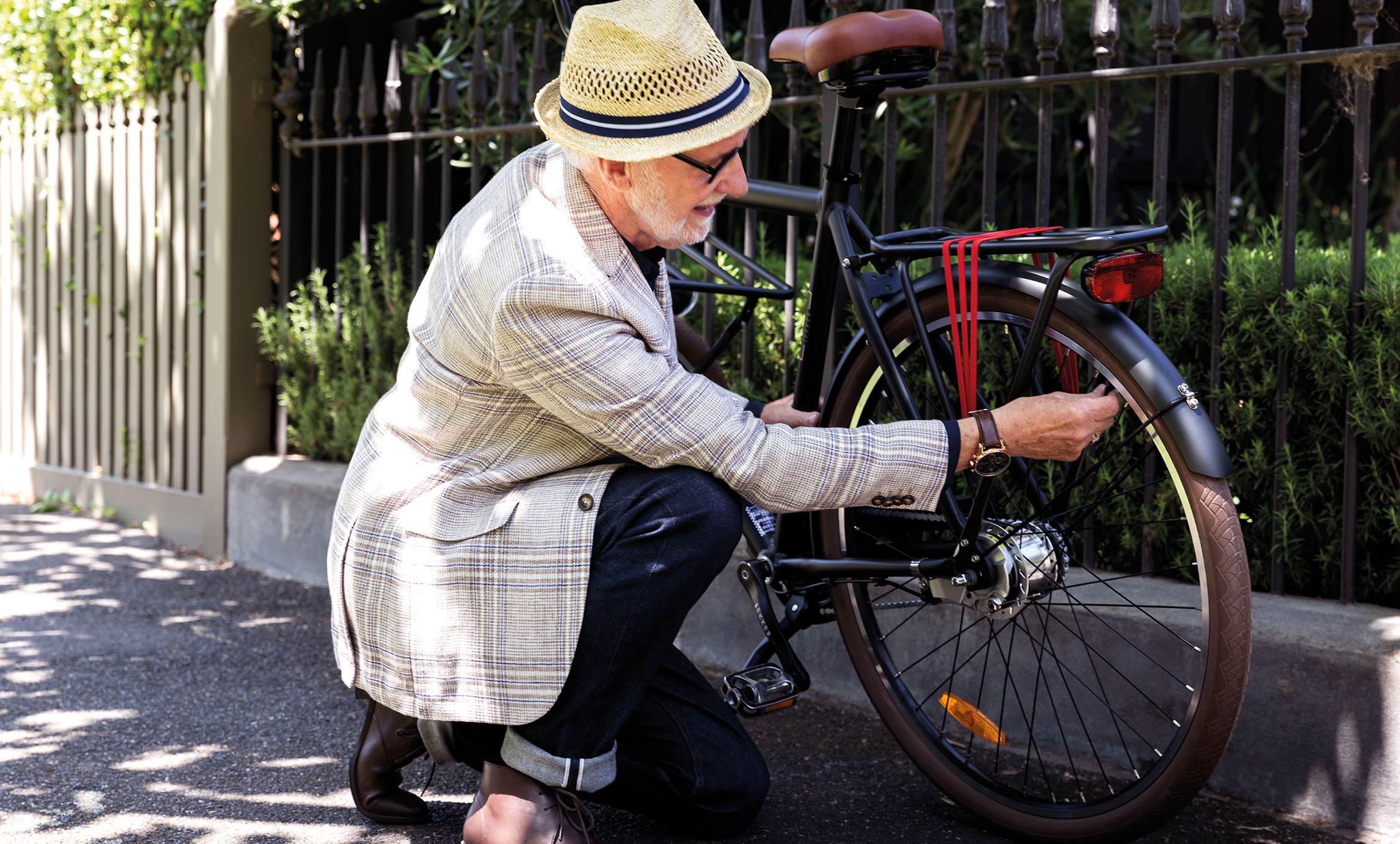 Senior man locking bicycle to fence